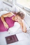 Mujer embarazada que lee un libro Imagen de archivo