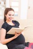 Mujer embarazada que lee un libro en casa Foto de archivo