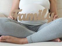 Mujer embarazada que lleva a cabo el mensaje de la familia Imagenes de archivo