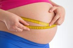 Mujer embarazada que lleva a cabo el metro aislado Conce de la dieta y de la atención sanitaria Imagen de archivo