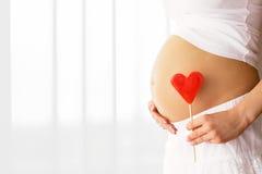 Mujer embarazada que lleva a cabo la muestra del corazón a un lado Imagen de archivo