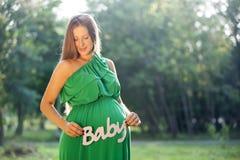 Mujer embarazada que lleva a cabo la palabra BEBÉ Imágenes de archivo libres de regalías