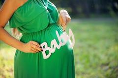 Mujer embarazada que lleva a cabo la palabra BEBÉ Fotografía de archivo