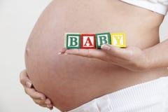Mujer embarazada que lleva a cabo los bloques de madera que deletrean al bebé Foto de archivo