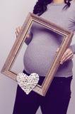 Mujer embarazada que lleva a cabo un corazón de los withs del marco Fotografía de archivo libre de regalías