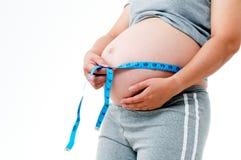 Mujer embarazada que mide su vientre Foto de archivo libre de regalías