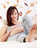 Mujer embarazada que miente en cama Imagenes de archivo