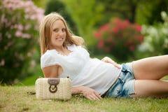 Mujer embarazada que miente en hierba Imagen de archivo