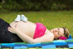 Mujer embarazada que miente en hierba verde Imagen de archivo libre de regalías