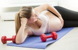 Mujer embarazada que miente en la estera de la aptitud y el vientre grande conmovedor Imagen de archivo