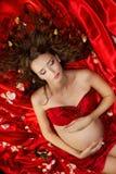 Mujer embarazada que miente en los pétalos color de rosa rojos fotografía de archivo