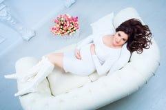 Mujer embarazada que miente en un sofá cerca de una cesta con los tulipanes Foto de archivo libre de regalías