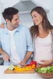 Mujer embarazada que mira al marido que taja verduras Foto de archivo libre de regalías