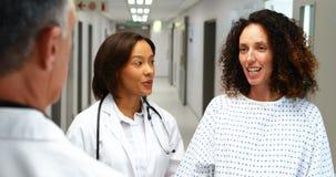 Mujer embarazada que obra recíprocamente con los doctores en pasillo almacen de video