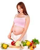 Mujer embarazada que prepara el alimento. Fotografía de archivo
