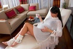Mujer embarazada que se reclina sobre el sofá Foto de archivo libre de regalías
