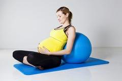 Mujer embarazada que se relaja contra bola de la aptitud Fotografía de archivo libre de regalías