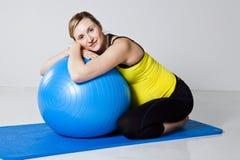 Mujer embarazada que se relaja contra bola de la aptitud Fotos de archivo