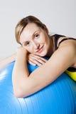 Mujer embarazada que se relaja contra bola de la aptitud Imagen de archivo