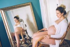 Mujer embarazada que se relaja en la mecedora fotos de archivo