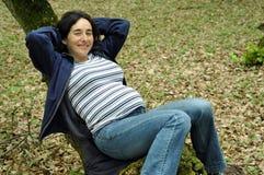 Mujer embarazada que se relaja en un árbol imagenes de archivo