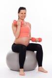 Mujer embarazada que se resuelve con pesas de gimnasia Imágenes de archivo libres de regalías