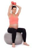 Mujer embarazada que se resuelve con pesas de gimnasia Fotos de archivo libres de regalías