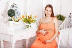 Mujer embarazada que se sienta cerca de un espejo en interior con ji lamentable Imagen de archivo