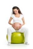 Mujer embarazada que se sienta en bola de la aptitud Imágenes de archivo libres de regalías