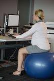 Mujer embarazada que se sienta en bola de la aptitud mientras que trabaja en el escritorio Fotos de archivo libres de regalías