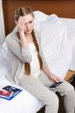 Mujer embarazada que se sienta en cama de hospital y que lleva a cabo la exploración del ultrasonido Imagen de archivo