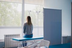 Mujer embarazada que se sienta en cama en sala cómoda, para doctor que espera de los jóvenes cuidadosamente Imagen de archivo libre de regalías