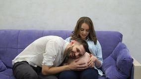 Mujer embarazada que se sienta en casa en el sofá con su televisión de observación del marido Un hombre comunica con su esposa y almacen de metraje de vídeo