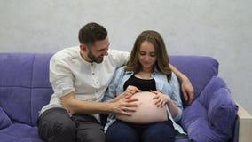 Mujer embarazada que se sienta en casa en el sofá con su televisión de observación del marido Un hombre comunica con su esposa y metrajes