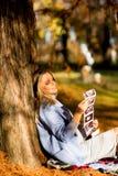 Mujer embarazada que se sienta en el parque del otoño Foto de archivo libre de regalías