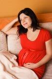 Mujer embarazada que se sienta en el sofá Imagenes de archivo