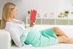 Mujer embarazada que se sienta en el sofá y la lectura Fotos de archivo libres de regalías
