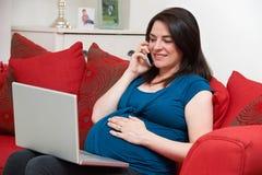 Mujer embarazada que se sienta en el teléfono de Sofa Using Laptop And Mobile imágenes de archivo libres de regalías