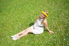 Mujer embarazada que se sienta en hierba con las flores alrededor de su cabeza Foto de archivo