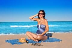 Mujer embarazada que se sienta en la arena azul de la playa Fotografía de archivo libre de regalías