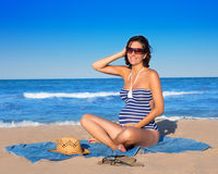 Mujer embarazada que se sienta en la arena azul de la playa Imágenes de archivo libres de regalías