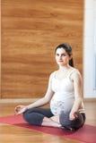 Mujer embarazada que se sienta en la estera de la yoga Fotografía de archivo