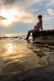 Mujer embarazada que se sienta en la orilla Imagenes de archivo