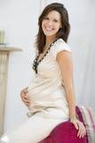 Mujer embarazada que se sienta en la sonrisa de la sala de estar Imagen de archivo libre de regalías
