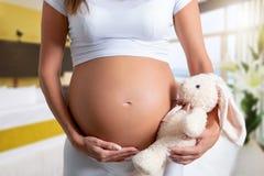 Mujer embarazada que se sostiene el vientre con un juguete del peluche imagen de archivo