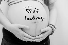 Mujer embarazada que se sostiene el vientre escribe la palabra que carga drenaje del ANG Imagenes de archivo
