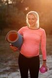 Mujer embarazada que sonríe en la cámara, llamarada del sol Foto de archivo
