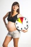 Mujer embarazada que sostiene el reloj de los meses Foto de archivo