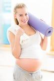Mujer embarazada que sostiene la estera de la yoga Foto de archivo libre de regalías