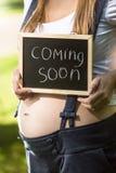 Mujer embarazada que sostiene la pizarra con el texto Foto de archivo